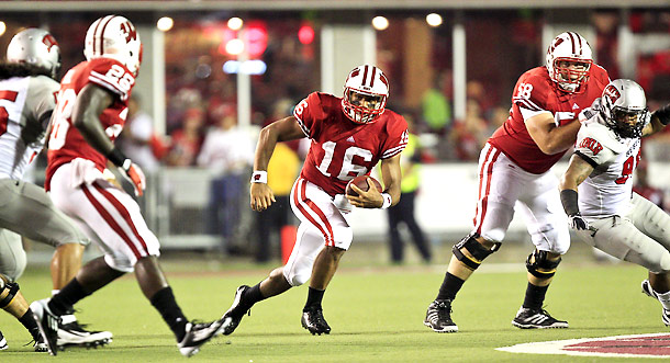 Wisconsin's Russell Wilson used the graduate transfer rule to spend his final year with the Badgers after playing previously for N.C. State. Photo via Sports Illustrated